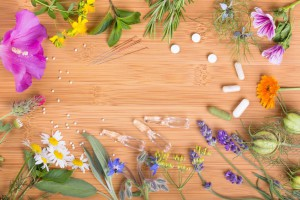 Alternative medicine background with flowers and leaves of medicinal plants, globules, acupuncture needles, pills, ampules